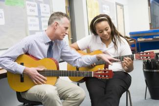 Guitar teacher with pupil